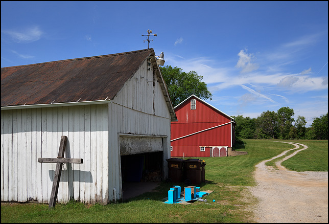 A white garage with a wooden cross leaning on it on Schwartz Road in rural Allen County, Indiana. A long gravel driveway winds past it toward a large red barn.