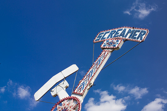 The signs on the top of the Screamer carnival ride.