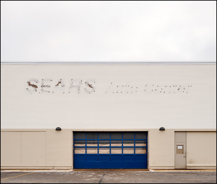 The signs on the auto center have been taken down on the closed Sears store at the Glenbrook Square Mall in Fort Wayne, Indiana. Brown paper covers the windows on the garage door.