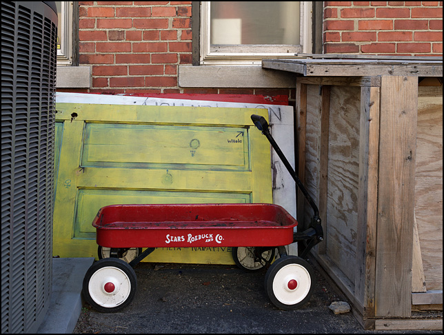 A child's red wagon sitting in front of some old doors next to a church in Indianapolis. The metal wagon, which is similar to a Radio Flyer red wagon, is labeled Sears Roebuck and Company.