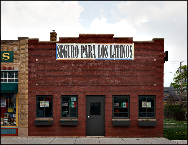 American and Mexican flags hang in the windows of Seguro Para Los Latinos, a Mexican insurance agent on Wells Street in Fort Wayne, Indiana.