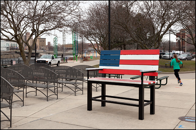 A giant park bench painted like the American flag, surrounded by normal sized benches, stands in Seitz Park in South Bend, Indiana. A female jogger is running around the back of the flag bench.
