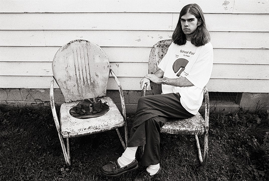 Self portrait of fine art photographer Christopher Crawford sitting on grandpas old rusty metal motel chairs.