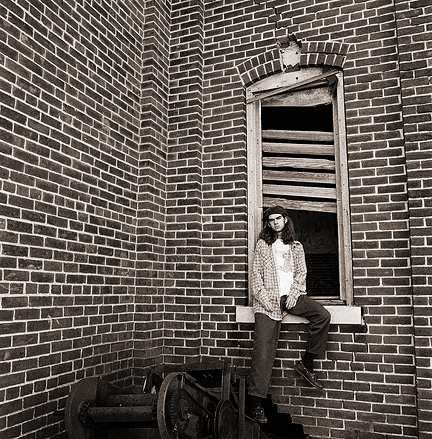 Self portrait of fine art photographer Christopher Crawford sitting in the window of an abandoned brick schoolhouse.