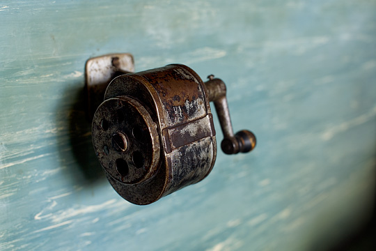 A rusty old manual pencil sharpener on a blue wall in grandpa's kitchen.