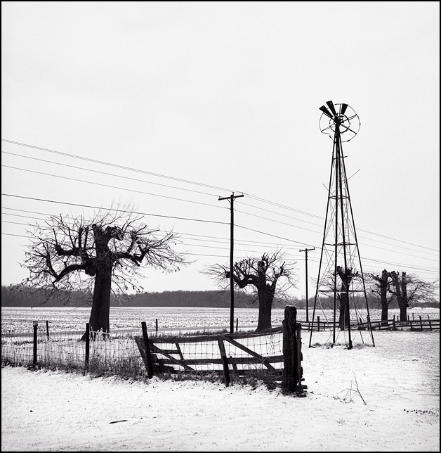 An old rusty windmill in an abandoned barnyard with a broken fence, all covered in snow during the cold Indiana winter.