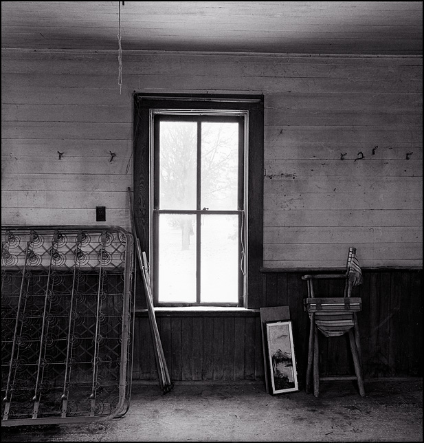 A set of antique bed springs, a folding chair, and a framed painting leaned against the wall under a window inside an abandoned summer kitchen in rural Indiana.