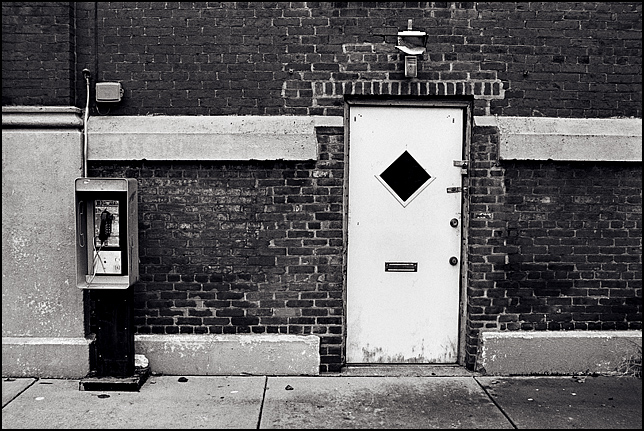 A payphone stands next to a door with four locks on it in the side of a rundown brick building along Shelby Street in downtown Louisville, Kentucky.