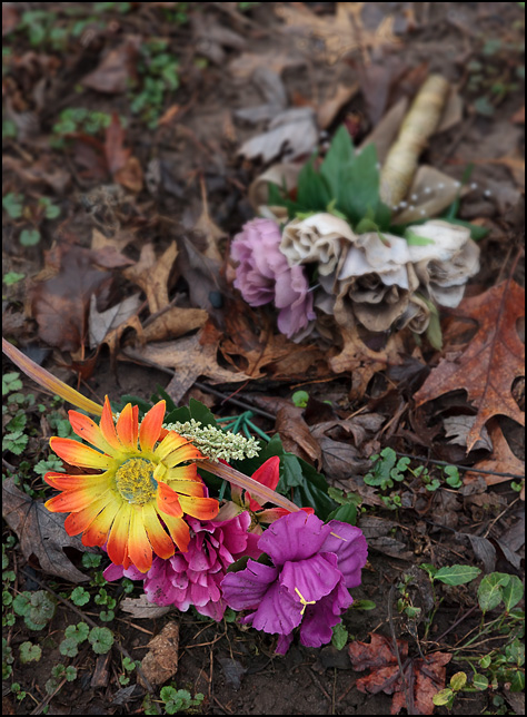 Two small bouquets of silk flowers lay on the muddy ground, surrounded by dead leaves.