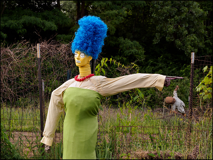 A Marge Simpson scarecrow at the Fort Wayne Parks and Recreation Community Garden on Bluffton Road in Fort Wayne, Indiana. An old broken baby doll hangs from her left hand.