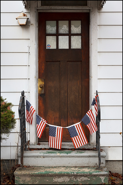 A string of American flags hanging from the handrails across the front steps of a small old white house on Sinclair Street in Fort Wayne, Indiana.