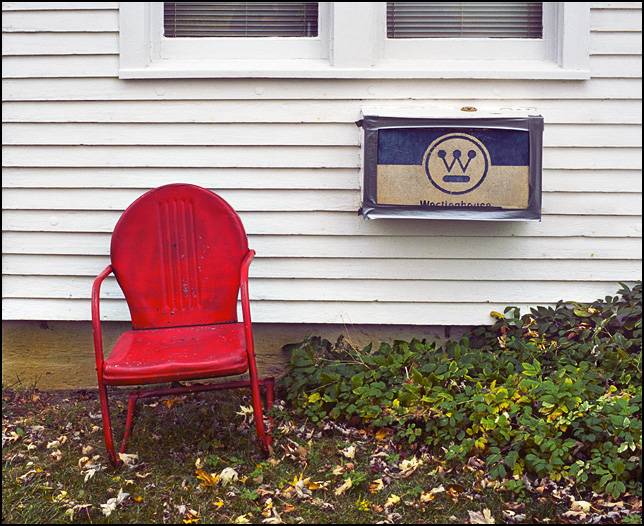 A red metal motel chair in front of an old white farm house with a Westinghouse window air conditioner in rural southwest Allen County, Indiana.