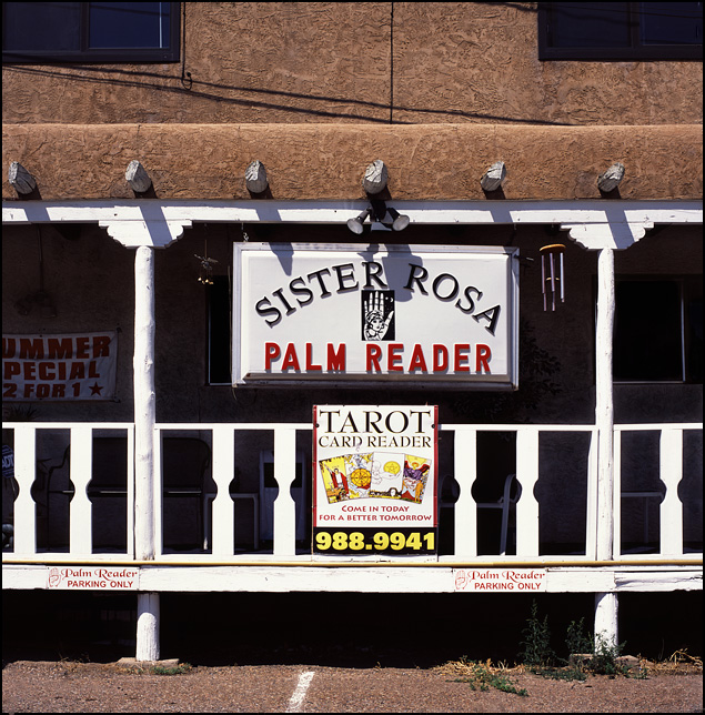 The front of Sister Rosa's Palm Readings shop on Saint Francis Drive in Santa Fe. The signs on the porch of the adobe building advertise Tarot card readings and a two for one summer special.