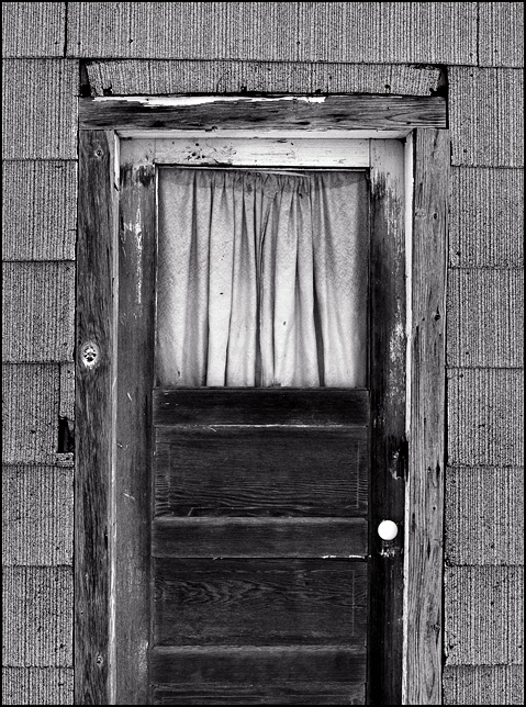An old weathered wood panel door with a curtain in the window on the side of an abandoned summer kitchen on Winters Road in rural Allen County, Indiana.