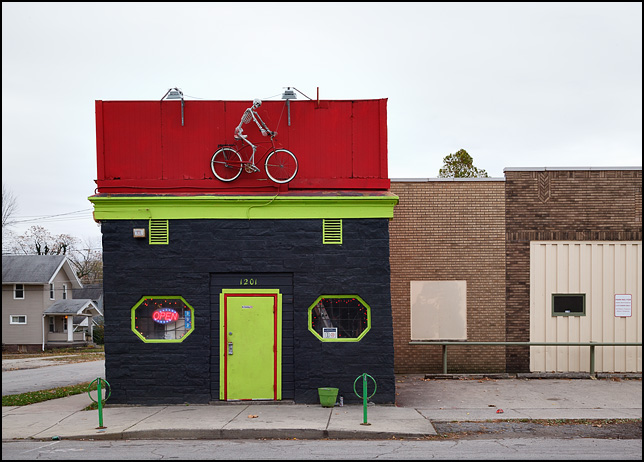 A life-size skeleton on a bicycle is mounted over the front door of Skeletunes Lounge on West Main Street in Fort Wayne, Indiana.