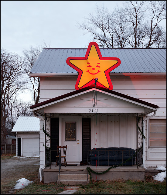 A giant yellow star with a smiling face mounted above the front porch of a house on Ardmore Avenue in Fort Wayne, Indiana. The star is from a Hardees restaurant sign and is being used as a Christmas decoration. The front porch has an old leather sofa to sit on!