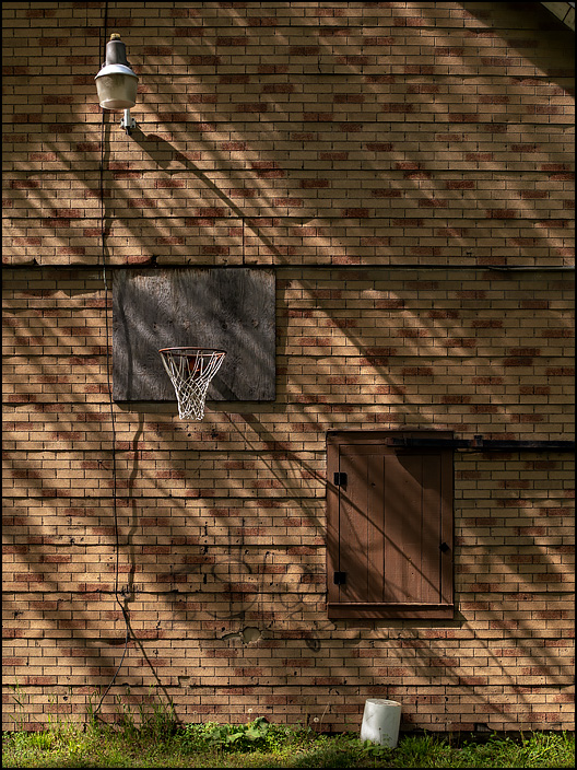 A basketball hoop on the side of an old barn with asphalt shingle siding and an old street light above the backboard. Located on the corner of Ardmore Avenue and Elmhurst Drive in Fort Wayne, Indiana.