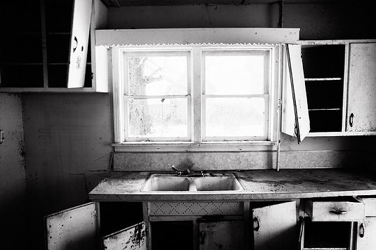 The broken cabinets and filthy sink in the kitchen of an abandoned house on Smith Road in Allen County, Indiana.