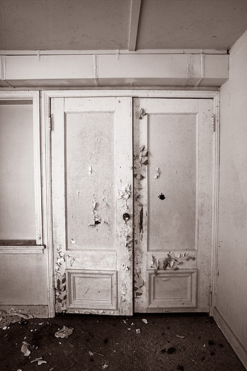 A pair of french doors with a bullet hole in one of them inside an abandoned house on Smith Road in rural Allen County, Indiana.