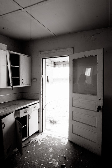Looking out the back door from the kitchen of an abandoned farmhouse on Smith Road in rural Allen County, Indiana. The window on the door is broken and the kitchen cabinets are torn up.