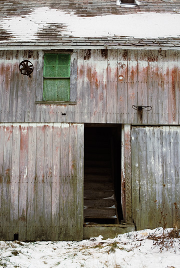 An old weathered abandoned barn in the winter with a basketball hoop over the door and a stairway to the second floor.