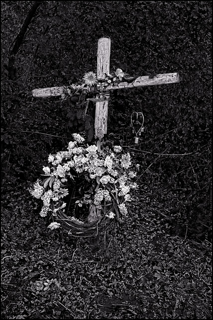 A large wooden roadside memorial cross adorned with a floral wreath stands in the woods along Smith Road in Fort Wayne, Indiana.