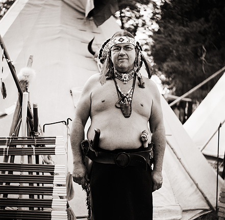Native American Dick Sutton stands in front of his tipi wearing traditional Indian clothing and headdress at the Johnny Appleseed Festival.
