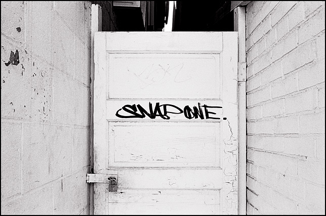 An old whitewashed wooden panel door with a graffiti tag that says SNAP ONE. The padlocked door closes off the space between two buildings on Wells Street in Fort Wayne, Indiana.