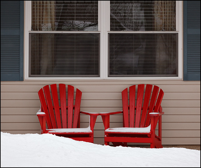 Two red adirondack chairs sit behind a pile of snow in front of a house.