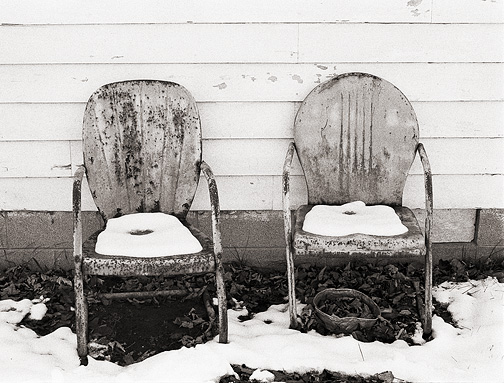 Snow covers a pair of rusty old metal motel chairs next to an old man's house in rural Allen County, Indiana.