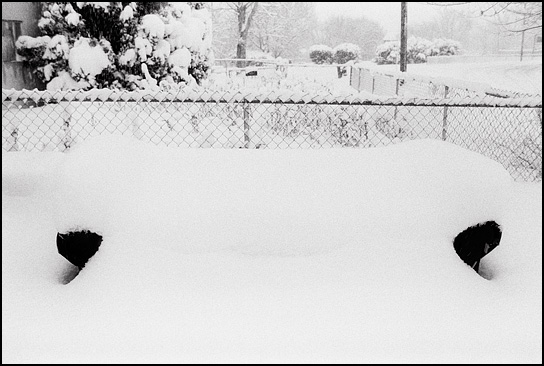 Snow covers an old sofa sitting outdoors after a blizzard in Santa Fe, New Mexico.