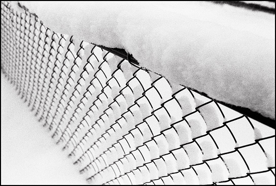 A chain link fence covered in snow during a heavy snowstorm in Santa Fe, New Mexico.