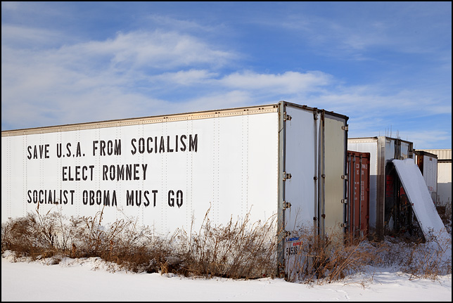 An old semi trailer with a political message stenciled on the side. Save USA from socialism, elect Romney, socialist Obama must go. It is on US-33 near Wolf Lake, Indiana.