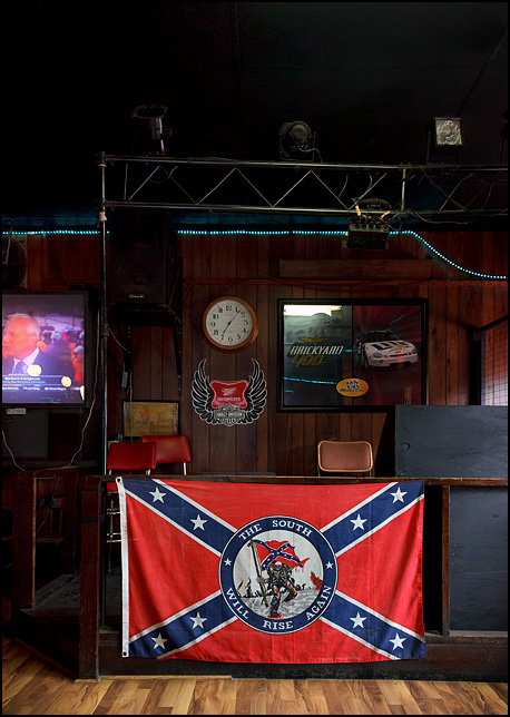 A Confederate flag with a roundel in the center that has a skeleton carrying a Confederate Flag, surrounded by the phrase, The South Will Rise Again. It hangs inside the Hitch-In-Post Tavern in Fort Wayne, Indiana.