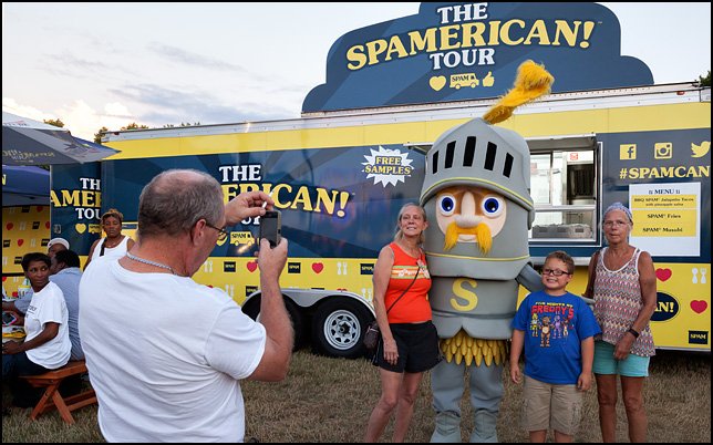 A man with a smartphone taking a picture of his family posing with Sir Can-A-Lot, a man in a medieval knight costume advertising SPAM meat in front of the Spamerican Tour trailer Three Rivers Festival in Fort Wayne, Indiana.