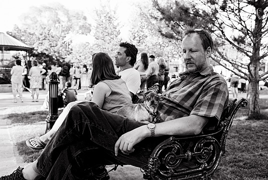 A man with a chihuahua on his lap sits on a park bench at the Santa Fe Plaza.