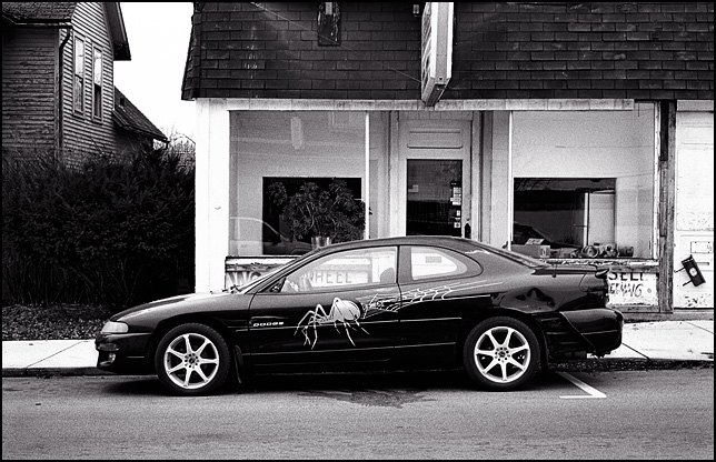 A Dodge Neon with a spider web and a black widow painted across the side of the car.