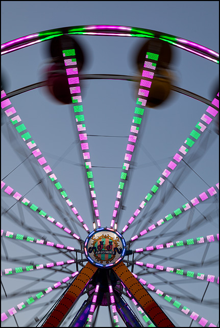 A spinning Ferris Wheel forms a blur of colorful lights at the Three Rivers Festival carnival in Fort Wayne, Indiana.