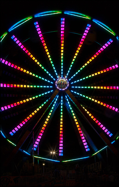 A rainbow of colored light radiates from the center of a spinning Ferris Wheel against the dark night sky at the 2016 Three Rivers Festival in Fort Wayne, Indiana.