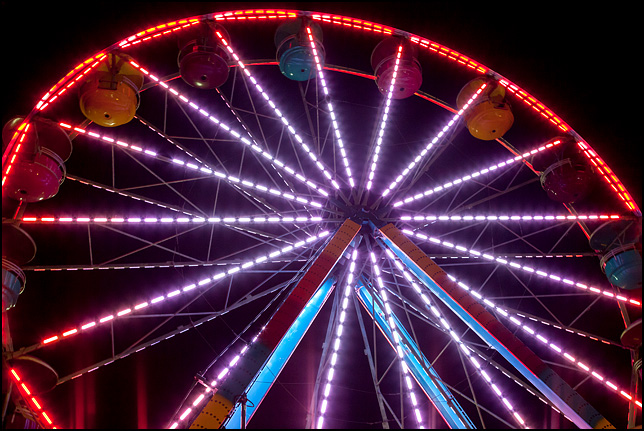 Colored lights outline a Ferris Wheel in motion against the black sky at the 2017 Three Rivers Festival in Fort Wayne, Indiana.