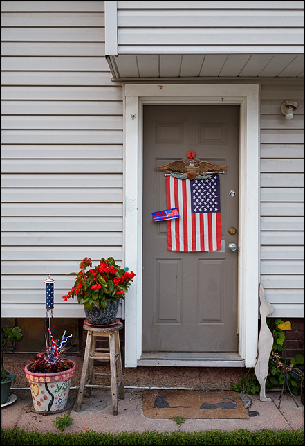 On the Fourth of July, an American flag hangs from a decorative Americana bald eagle on the side door of a house on Spy Run Avenue in Fort Wayne, Indiana. A bumper sticker on the door says, God Bless America.