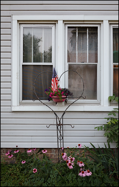 An American flag and flowerpot in a heart shaped wrought-iron plant hanger in front of a house with daisies growing under the window in Fort Wayne, Indiana.