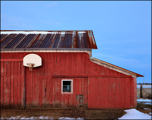 An old red barn with a basketball hoop at sunset on a farm on State Road 1 in rural Allen County, Indiana.