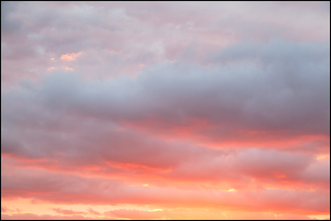 Abstract photograph of bands of clouds against an orange sunset sky in rural Elkhart County, Indiana.