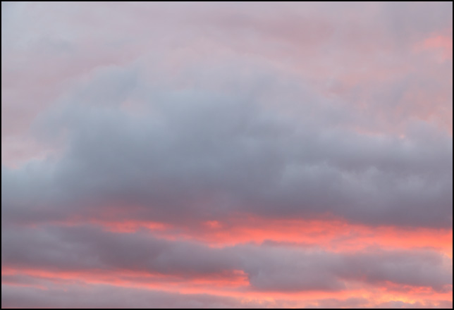Abstract photograph of bands of dark clouds against a red and purple sunset sky in rural Elkhart County, Indiana.