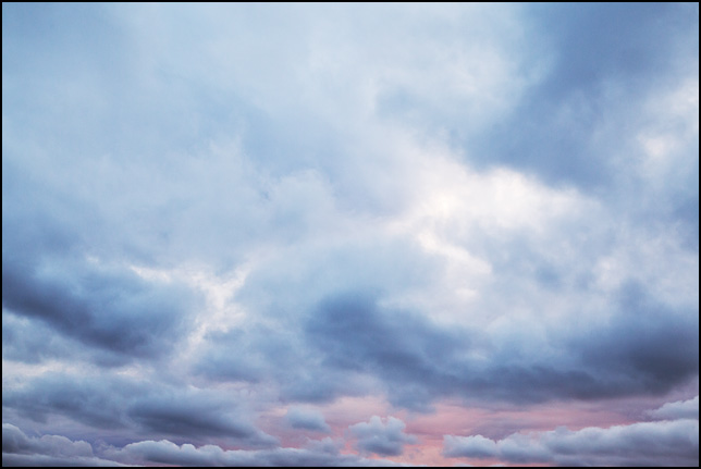 Abstract photograph of white light breaking through dark blue clouds against a colorful sunset sky in rural Elkhart County, Indiana.