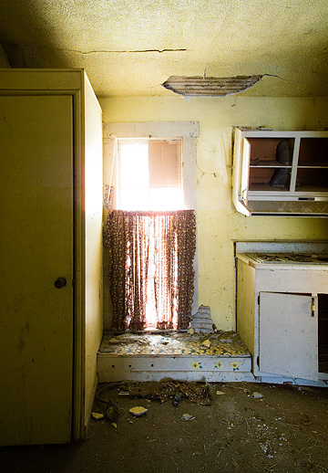 Broken cabinets with daisy flower stickers next to a window with torn curtains in the dilapidated kitchen of an abandoned house.