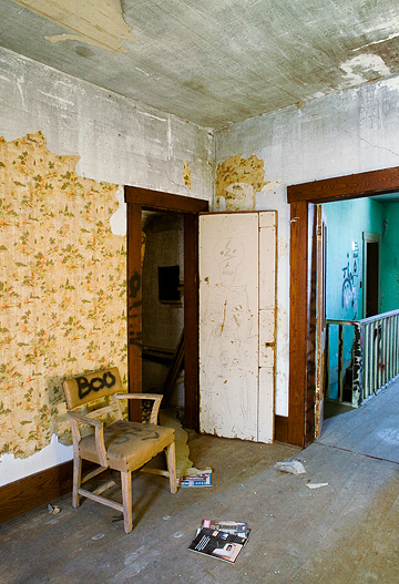 Graffiti covers the walls and furniture of an upstairs bedroom with old magazines on the floor in an abandoned farmhouse. The chair has BOO spray painted on it.