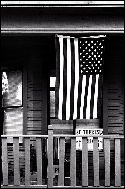 A large American flag hangs from the front porch of a house on Jefferson Boulevard in downtown Fort Wayne, Indiana. A sign that says Saint Therese Catholic School Pride hangs in the window.