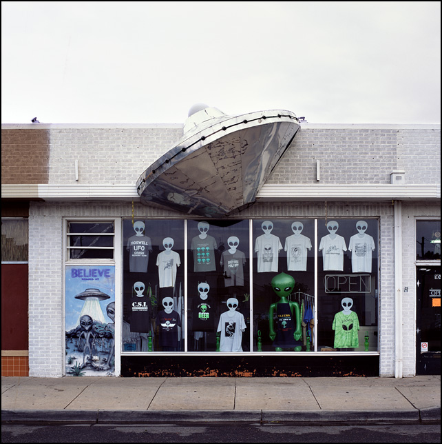 A UFO flying saucer sticking out from the front of the Starchild store in Roswell, New Mexico. The door has a painting of aliens emerging from their spaceship under a sign that says Believe.